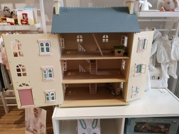 Big wooden dollhouse that opens up and has stairs you can move around. The roof also comes off!